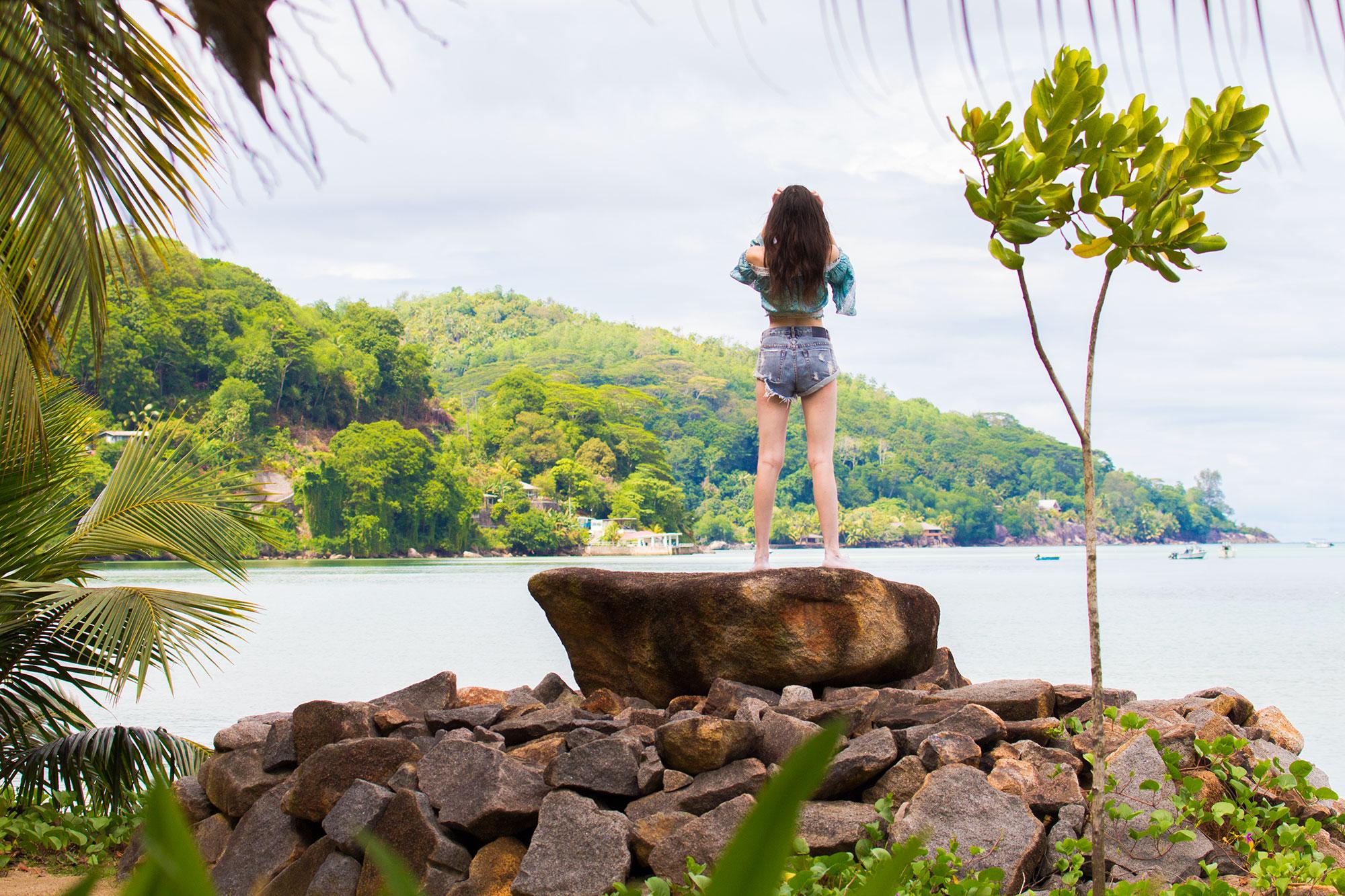 Ella on boulder by ocean on Mahe island, Seychelles